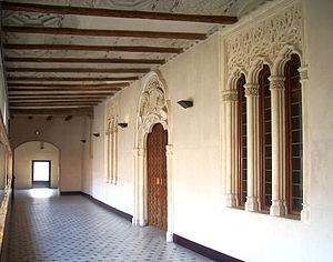 Corredor de acceso a las salas nobles del Palacio de los Reyes Católicos. A la derecha, portada de la entrada principal.